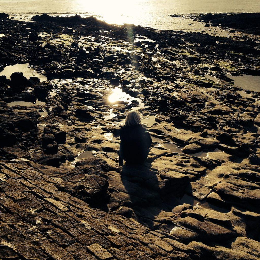 woman-on-rocks-water (1280x1280)