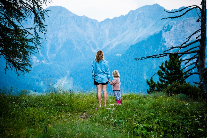 Mother with girl by mountains